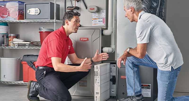 HVAC expert discussing the benefits of regular Furnace Maintenance with the homeowner