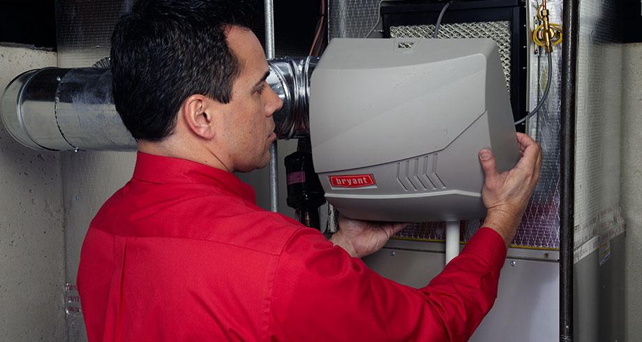 HVAC technician installing a whole-home humidifier